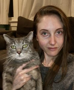photo of Nicole Pagowsky, a white woman with long hair. She is holding a tabby cat.