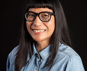 Headshot of Ione Damasco wearing a light blue shirt and black rimmed glasses.
