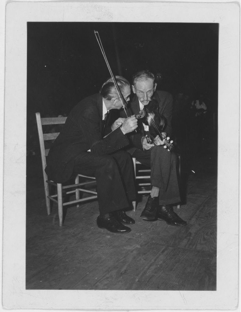Fiddling Bill Hensley and his rival for Old Time Fiddlers' Championship, Asa Helton, both seated and talking, holding their fiddles, at the Mountain Music Festival, Asheville, North Carolina